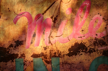 holed: Rusty metal sign weathered and in shade with only partial words visible