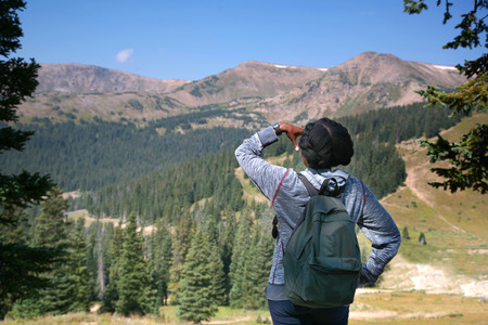 Young black female tourist views mid-day landscape of mountains with evergreens and   deep blue sky