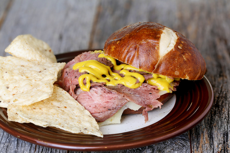 flank: Flank steak sandwich with pretzel bun and mustard and chips on weathered table top Stock Photo