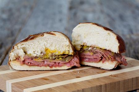 pretzel: Flank steak sandwich with pretzel bun and mustard on weathered table top Stock Photo