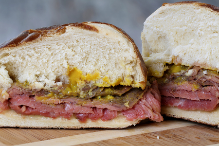 flank: Flank steak sandwich with pretzel bun and mustard on weathered table top Stock Photo