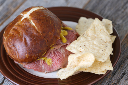 pretzel: Flank steak sandwich with pretzel bun and mustard and chips on weathered table top Stock Photo