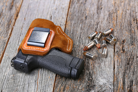 carry on: Automatic Handgun with leather holster and bullets on a wooden background.