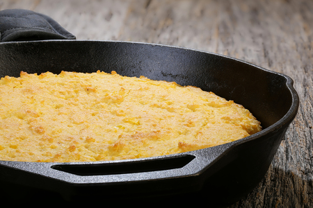 corn flour: Corn bread baked in flat iron skillet displayed on a rustic table Stock Photo