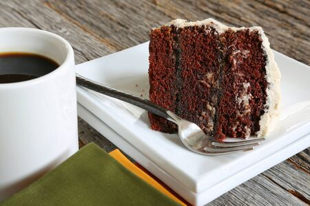 three layer: A slice of homemade three layer chocolate cake with vanilla and coffee icing
