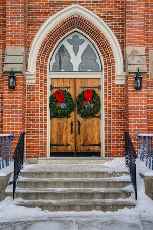 Gothic oak wooden church doors with ornate metal hardware, wreath, and red bow