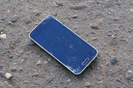 Smartphone with a broken display on the ground