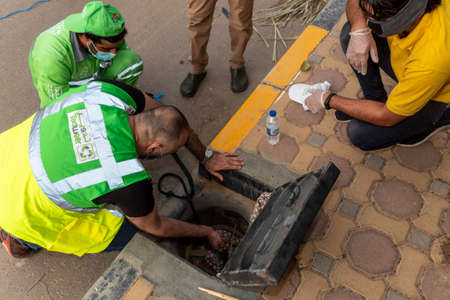 Al Ain, United Arab Emirates 07/09/2020 : A group of private and governmental personnel gather together during Covid-19 to rescue a kitten from a sewer drain pipe on 45 degree Celsius heat