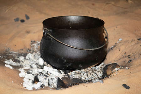 A South African Potjiekos pot standing in a hot BBQ in the UAE desert