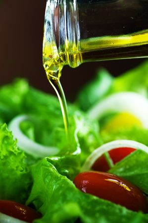 Healthy Salad and Pouring Olive Oil closeup photo