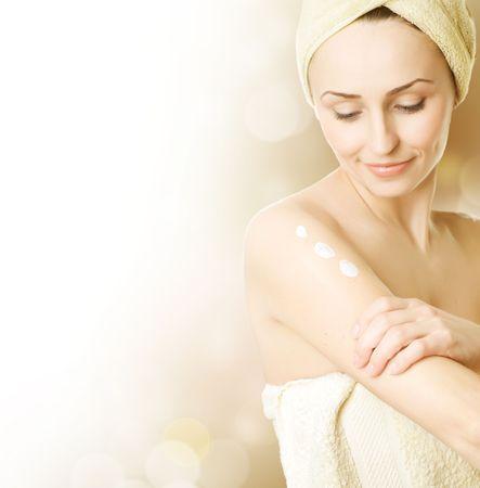 Beautiful Young Woman applying moisturizer Stock Photo - 6683197