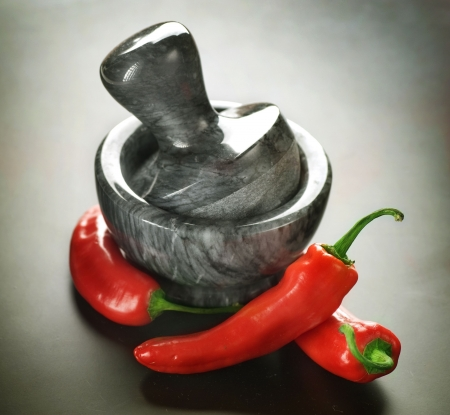 chilli: Mortar with pestle and Herbs.Over black background