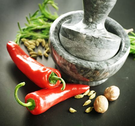 indian cooking: Mortar with pestle and Herbs.Over black background