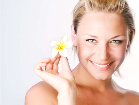 Beautiful Healthy Young Woman with frangipani flower.Spa photo