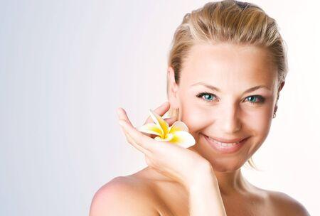 mujer rubia desnuda: Hermosa mujer de j�venes saludables con flor de frangipani.Spa