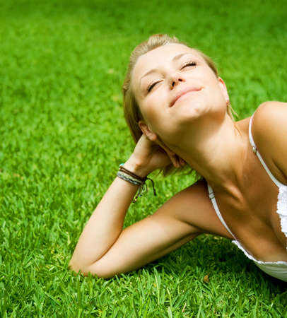 Beautiful Young Woman lying on the grass photo