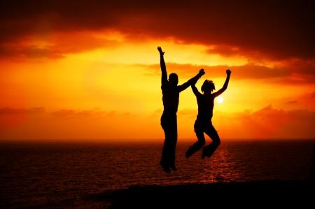 夕日を背景に幸せなジャンプのカップル。休暇の概念 写真素材