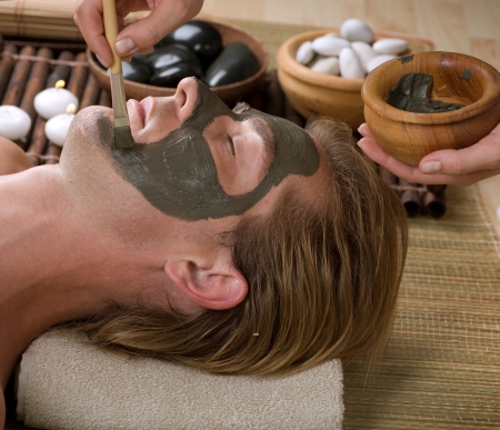 skincare facial: Spa. Handsome Man with a Mud Mask on his Face  Stock Photo