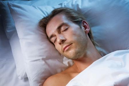 durmiendo: Hombre guapo dormido en su cama