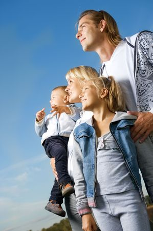 family looking up: Healthy Family Outdoor.Happy Father with Kids over blue sky