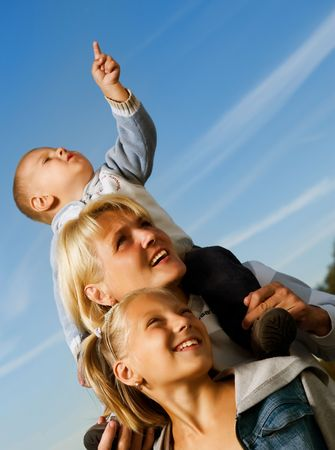 Look: Happy Mother with Kids over blue sky . Family outdoor