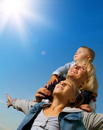 Happy Mother with Kids over blue sky . Family outdoor photo