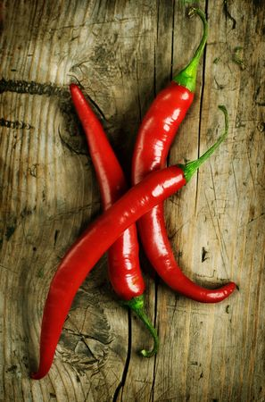 red chilli pepper plant: Red Hot Chili Peppers over wooden background