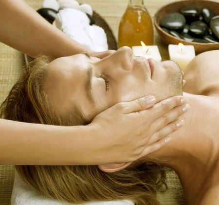 Spa.Young Man getting Face Massage. photo