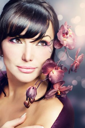Beautiful Healthy Woman with Orchid flower photo
