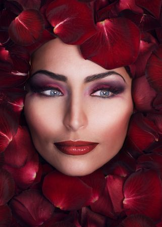 woman's: Beautiful Womans Face and rose petals.Perfect Skin