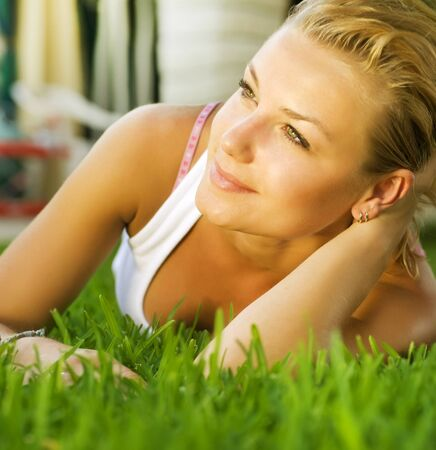 Beautiful healthy Young Woman lying on the green grass photo