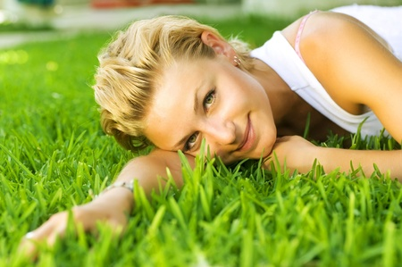 Beautiful healthy Young Woman relaxing on the green grass Stock Photo