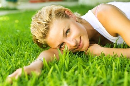 Hermosa joven saludable relajante sobre la hierba verde