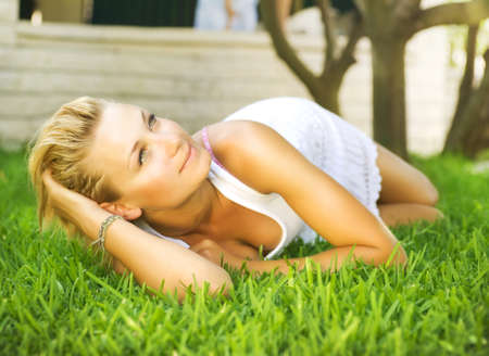 Beautiful healthy Young Woman relaxing on the green grass  photo