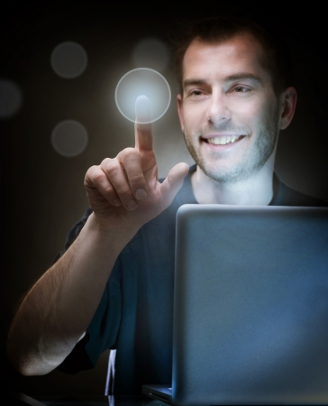 Young Man With Laptop pushing the button Stock Photo - 9378952