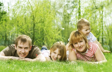Happy Family outdoor lying on green grass photo