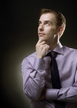 actitudes: Empresario guapo pensamiento. Fondo negro