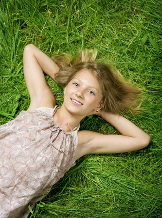 Cute happy Girl lying on a green grass photo