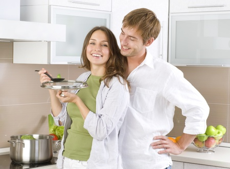 utensil: Young happy couple cooking together at home kitchen Stock Photo