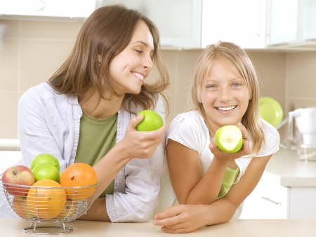 Happy Mother with Daughter eating Healthy food. Diet photo