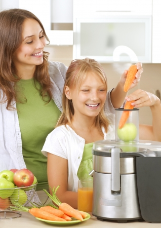 Happy Family making fresh apple and carrot juice photo