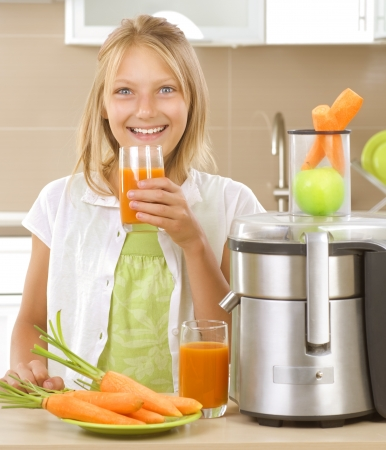 extractor: Girl drinking fresh carrot and apple juice. Healthy lifestyle Stock Photo