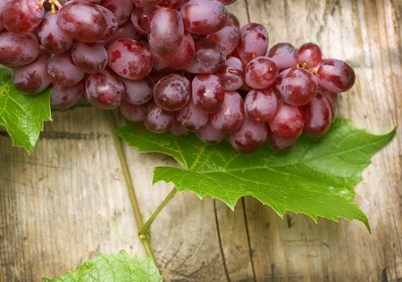 wine and grapes: Bunch of grapes over Wood Background
