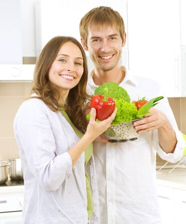 Young happy couple cooking together at home kitchen Stock Photo - 10371276