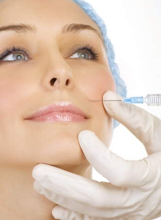 salon background: Woman gets cosmetic injection of botox. Beauty Treatment Stock Photo