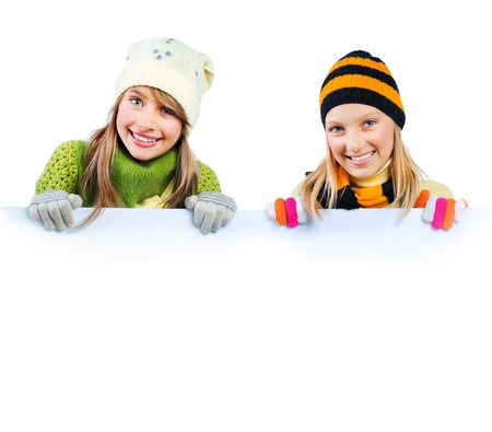 ropa de invierno: Chicas guapas teniendo billboard signo en blanco. Espacio para el texto