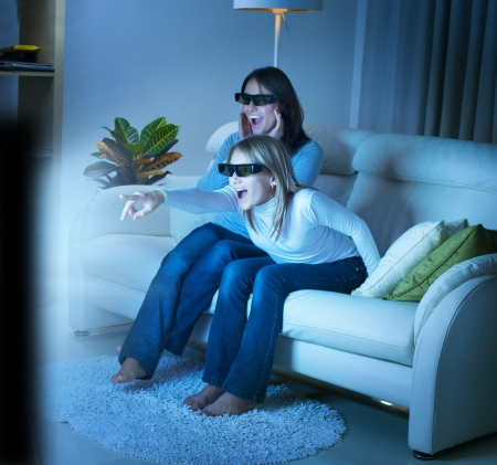 lcd tv: Mother with Daughter watching 3d film on TV