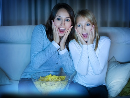 family movies: Mother with Daughter watching film on TV  Stock Photo