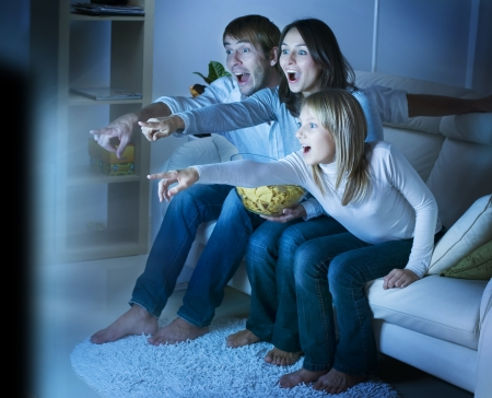 personas viendo tv: Familia viendo la televisi�n. Verdaderas emociones