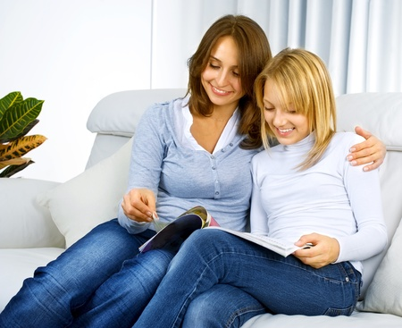 Mother with Teenage Daughter reading Magazine  photo